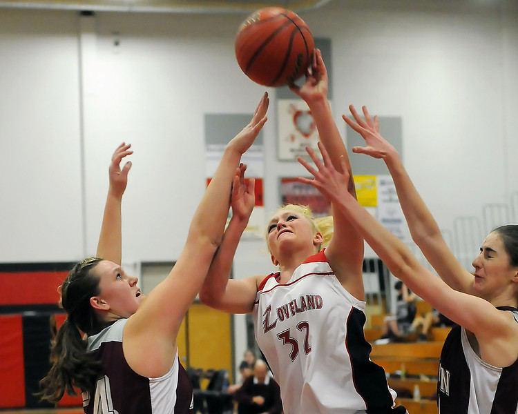Loveland High School senior Shelby Jones attempts to get a shot off between Horizon defenders Kaylie Rader, left, and Jaque Malcolm-Peck in the third quarter of their game on Tuesday, Feb. 9, 2010 at LHS.