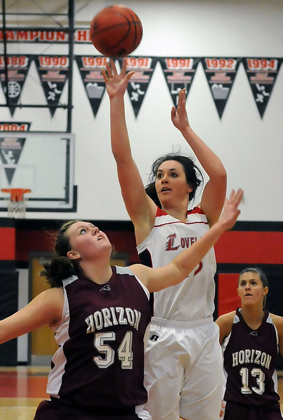 Loveland High School's Katie Patterson shoots a jump shot between Horizon's Kaylie Rader, left, and Rachel Bollinger during their game on Tuesday, Feb. 9, 2010 at LHS.