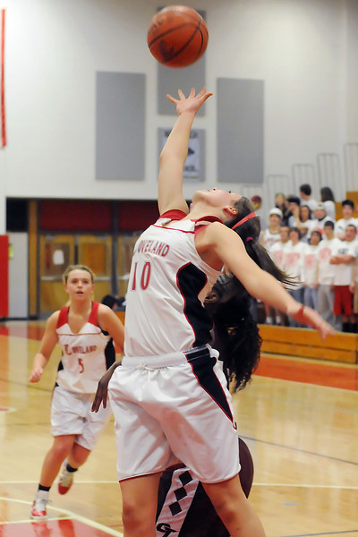 Loveland High School sophomore Cassidy Smith (10) goes up for a rebound over Cherokee Trail's Essence Shead while teammate Bradey King looks on in the second quarter of their game