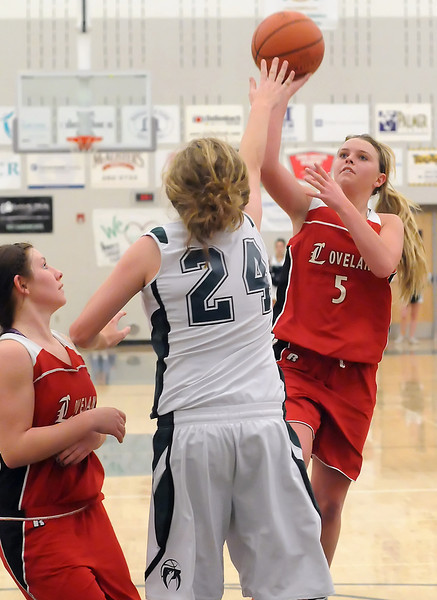 Loveland High School sophomore Bradey King (5) puts up a shot over Fossil Ridge's Kylee Willer while Colissa BAkovich looks on in the fourth quarter of their game Tuesday at FRHS. The Indians won, 53-50.
