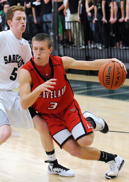 Loveland High School senior Taylor Svendsen (3) drives around Fossil Ridge's Adam Tynan in the first quarter of their game Tuesday at FRHS. The Indians lost, 74-67.