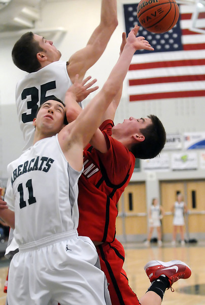 Loveland High School senior Cam Michael, right, collides with Fossil Ridge defenders Zach Chavez-LeVett (11) and Garrett Bryant (35) while attempting a shot in the lane in the fourth quarter of their game Tuesday at FRHS. The Indians lost, 74-67.