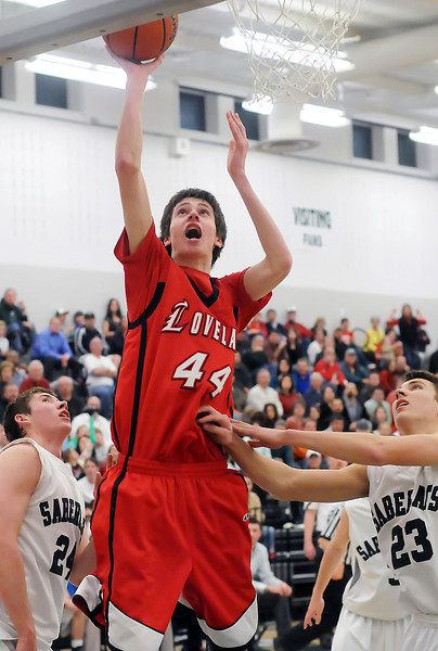 Loveland High School sophomore Conor Lang (44) puts up a shot between Fossil Ridge's Chris Hansen, left, and Clayton Kuchta in the second quarter of their game Tuesday at FRHS. The Indians lost, 74-67.
