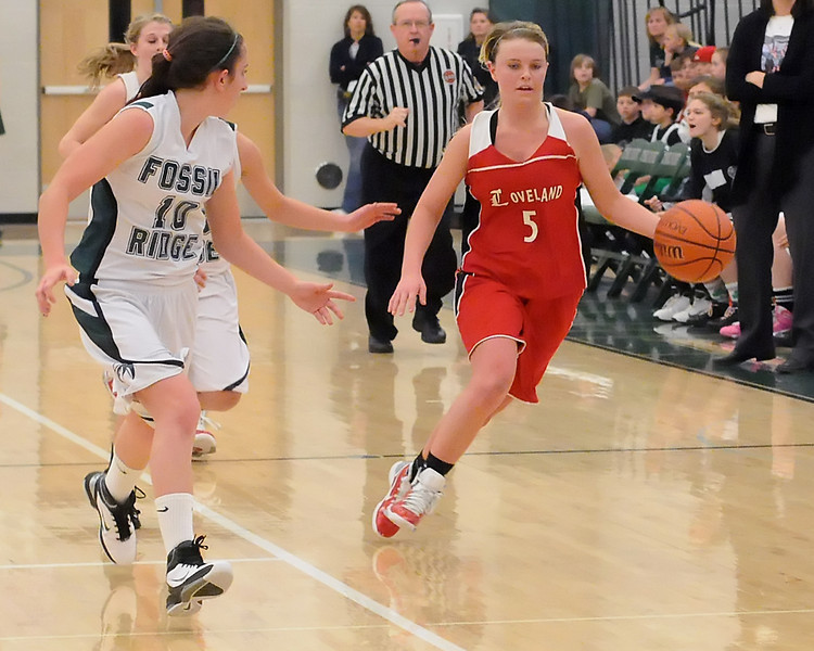 Loveland High School sophomore Bradey King (5) dribbles around Fossil Ridge's Brittany Younan (10) in the fourth quarter of their game Tuesday at FRHS. The Indians won, 53-50.