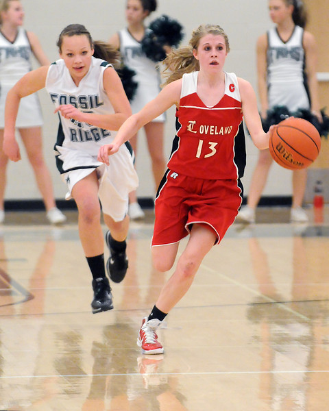 Loveland High School senior Stephanie Hutsell (13) dribbles ahead of Fossil Ridge defender Savannah Smith in the fourth quarter of their game Tuesday at FRHS. The Indians won, 53-50.