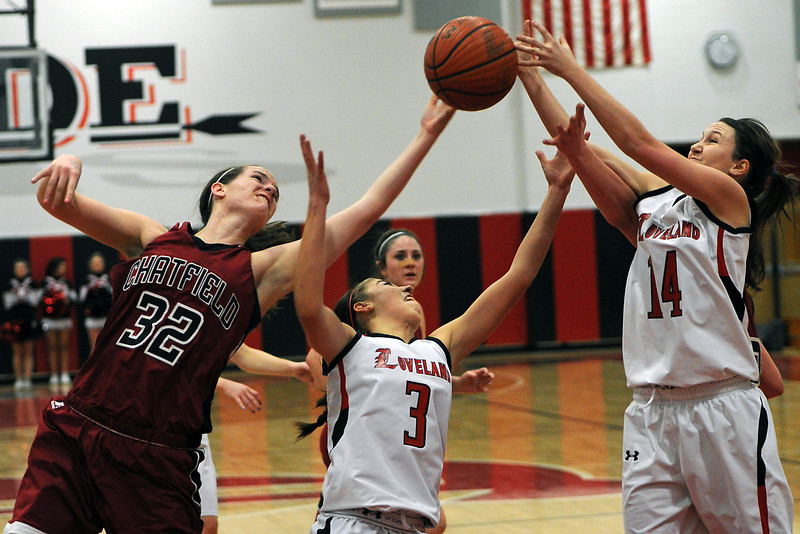 Loveland High School teammates Kylie McCaffery, right, and Allison Gleason battle for a reboune with Chatfield's Kristi Vaninger in the second quarter of their game on Wednesday, Feb. 22, 2012 at LHS.