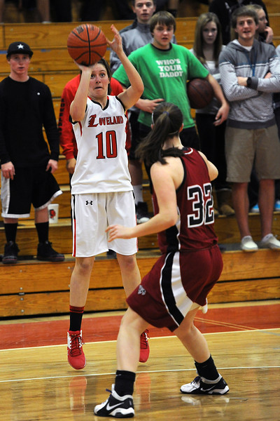 Loveland High School junior Cassidy Smith, left, shoots a 3-pointer over Chatfield's Kristi Vaninger in the third quarter of their game on Wednesday, Feb. 22, 2012 at LHS.