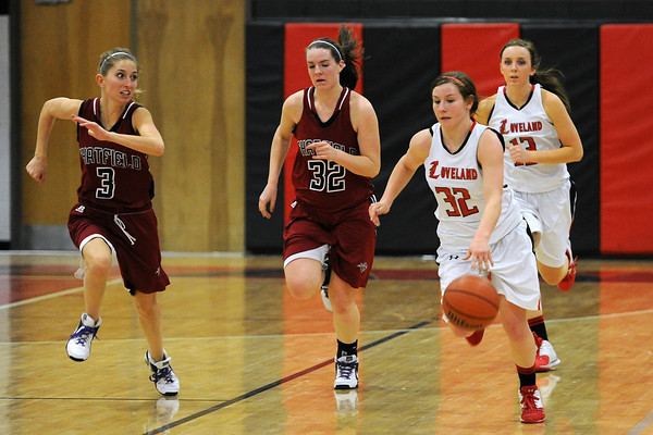 Loveland High School junior Colissa Bakovich (32) brings the ball upcourt ahead of Chatfield's Sarah Lewnard, left, and Kristi Vaninger and teammate Brooke Nyenhuis in the third quarter of their game on Wednesday, Feb. 22, 2012 at LHS.