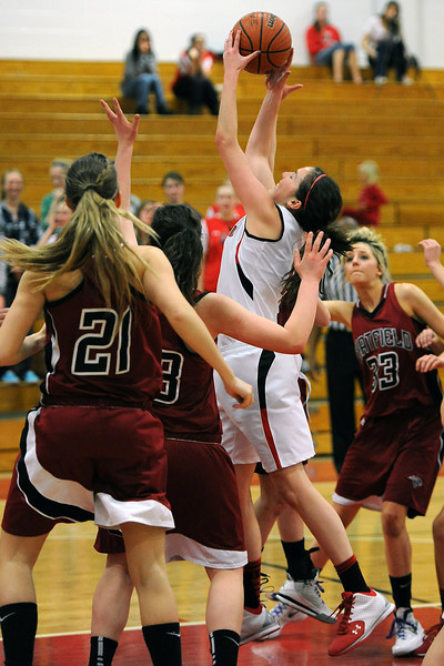 Loveland High School junior Lauren Spencer, middle, pulls down a rebound traffic in the third quarter of a game against Chatfield on Wednesday, Feb. 22, 2012 at LHS.