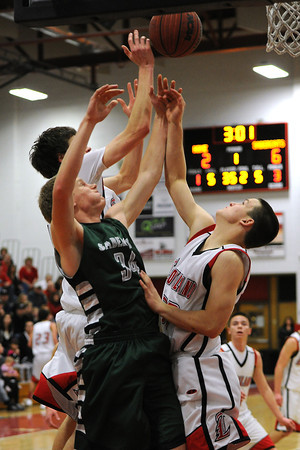 Fossil Ridge High School junior Corey Peter (34) battles for a rebound with Loveland's Jacob Weinmaster, right, and Conor Lang in the first quarter of their game Tuesday, Feb. 14, 2012 at LHS.