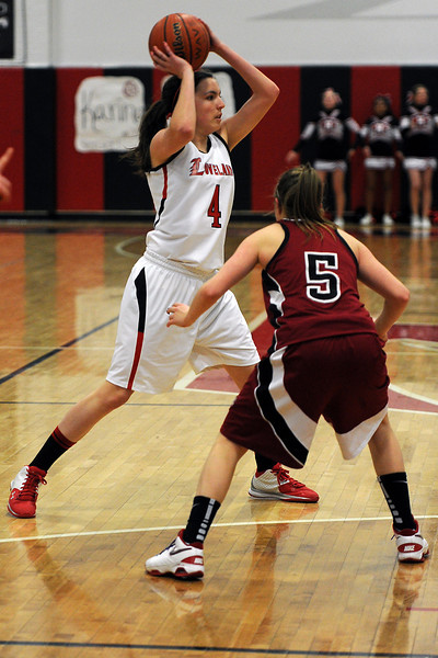 Loveland High School junior Lauren Spencer, left, looks for an open teammate while being guarded by Chatfield's Kelsi Lawrence in the second quarter of their game on Wednesday, Feb. 22, 2012 at LHS.
