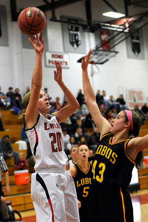 Loveland High School senior Karina Schlecht, left, puts up a shot over Rocky Mountian's Kelsey Bedard in the first quarter of their game Thursday, Feb. 9, 2012 at LHS.