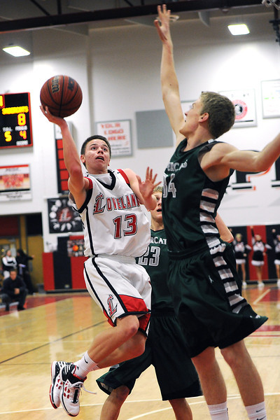 Loveland High School junior joe Etling, left, attempts a shot while being defended by Fossil Ridge's Corey Peter, right, and Alex Semadeni in the first quarter of their game Tuesday, Feb. 14, 2012 at LHS.