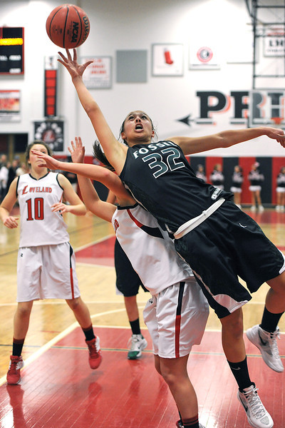 Fossil Ridge High School junior Lauren Roeling (32) battles for a rebound with Loveland's Bradey King while Cassidy Smith, left, looks on in the third quarter of their game Tuesday, Feb. 14, 2012 at LHS.