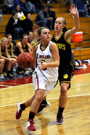 Loveland High School junior Bradey King, left, drives to the basket around Rocky Mountain's Kimberly Catlett during their game Thursday, Feb. 9, 2012 at LHS.