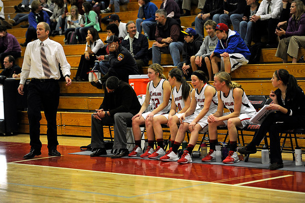 Loveland High School girls head basketball coach Chris Michael, left, and varsity players look on during a game against Rocky Mountain on Thursday, Feb. 9, 2012 at LHS.