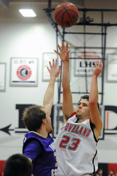 Loveland High School senior Adam Kinnes, right, puts up a shot over Fort Collins defender Mitch Yancey in the second quarter of their game Tuesday, Feb. 7, 2012 at LHS.