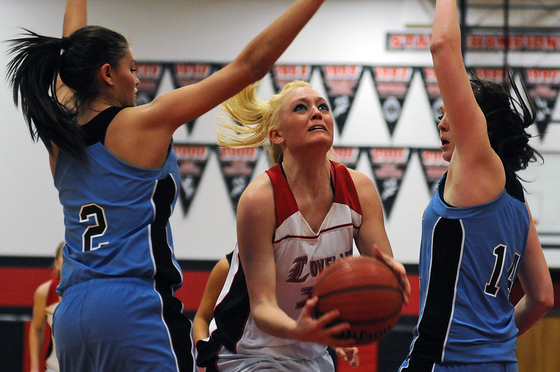 Loveland High School senior Shelby Jones, center, drives toward the basket between Mountain Range High School junior Kristen Ward, left, and sophomore Holly Hatfield during Thursday night's game at Loveland High School. Loveland won the game 55-37.