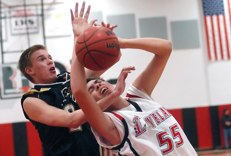 Loveland High School junior Jim Etling is fouled by Legacy's Tim Schmuhl as he goes up for a shot in the second quarter of their game on Tuesday, Jan. 12, 2010 at LHS. Loveland won, 67-43.