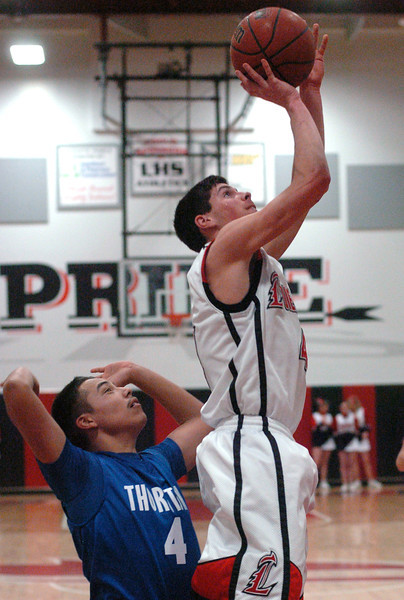 Loveland High School senior Michael Kielar takes a shot in front of Thornton's Ivan Macias in the second quarter of their game on Friday, Jan. 29, 2010 at LHS. Loveland won 71-40.