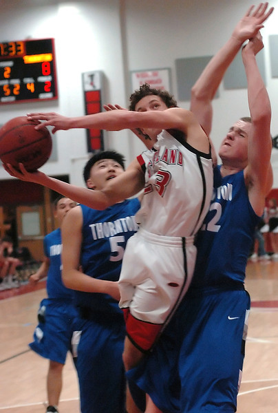 Loveland High School senior Seth Good drives to the basket between Thornton defenders Petr Rossiytsev, right, and Justin Nam in the second quarter of their game on Friday, Jan. 29, 2010 at LHS. Loveland won 71-40.