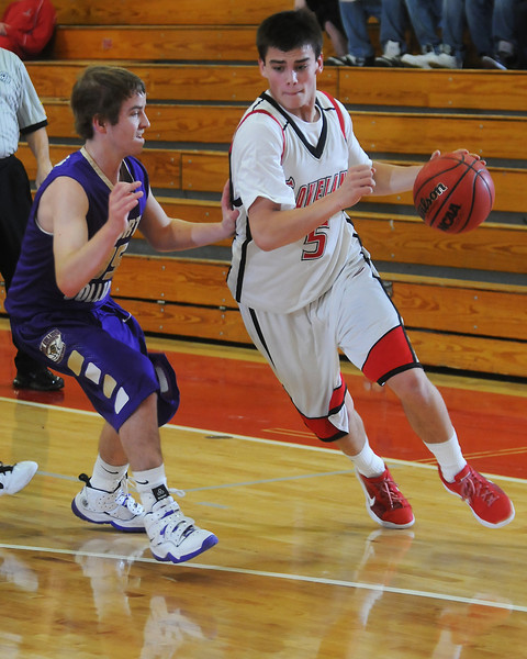 Loveland High School senior Cam Michael drives to the basket around Fort Collins defender Kollin Fleener in the second quarter of their game Friday night at LHS.