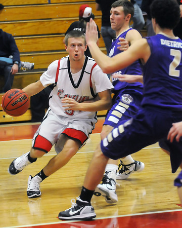 Loveland High School senior Taylor Svendsen drives to the basket past Fort Collins defenders Ben Marum, back right, and Derek Dietrich in the fourth quarter of their game Friday at LHS.