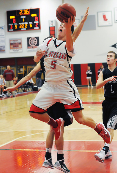 Loveland High School senior Cam Michael (5) takes a shot in front of Fossil Ridge's Heath Brashear (1) and Garrett Bryant in the first quarter of their game on Thursday, Jan. 13, 2011 at LHS. The Indians lost,