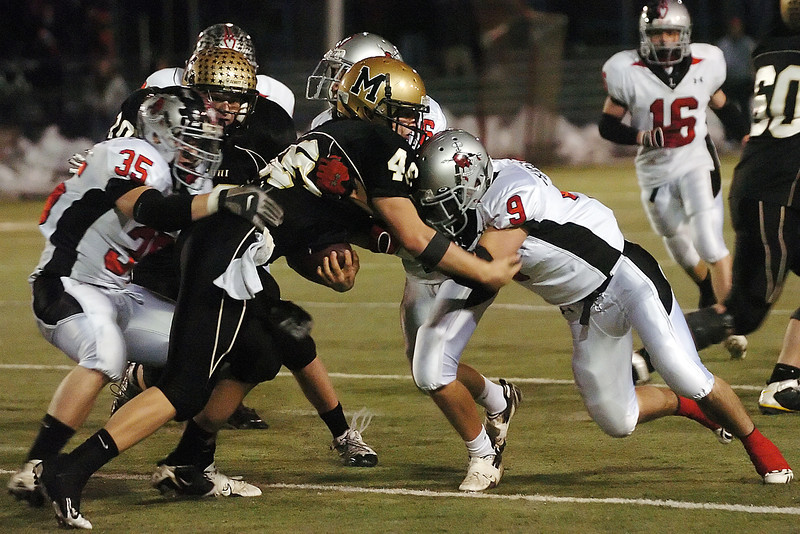 Loveland High School defenders Dillon Lawrence (35), A.J. Steele (6) and Shayn Herndon (9) tackle Monarch's Conner Dunn in the fourth quarter of their Class 4A state quarterfinal game on Friday, Nov. 20, 2009 in Lafayette.