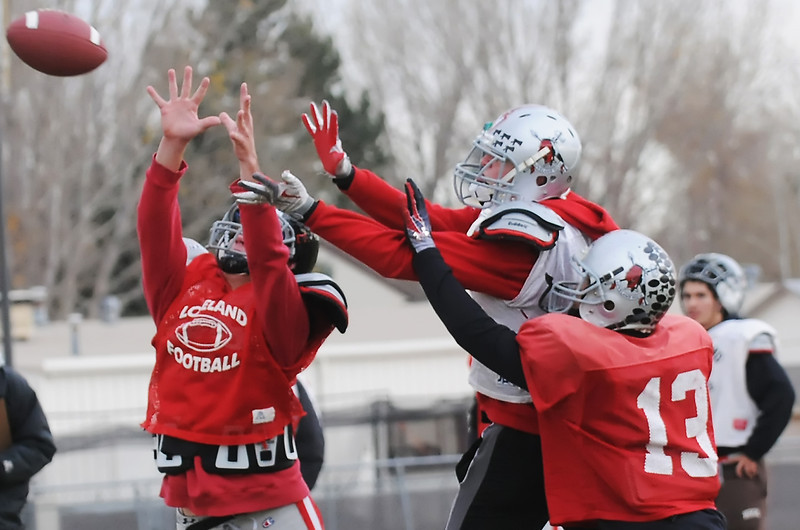 Loveland High School safety Scott Weissmann, left, and cornerback Taylor Appleby, right, defend on a pass play to wide receiver Kirk Shaw during football practice Wednesday afternoon.