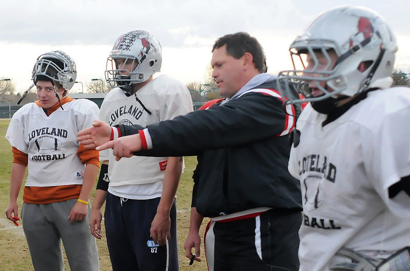 Loveland High School linebackers coach Ron Ouimet goes over a drill with players during practice Wednesday afternoon outside the school. From left are Ben Johnson, Zach LeBaron, Ouimet, and Derek Eppel.