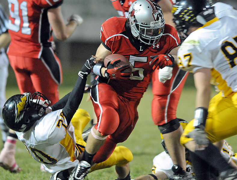Loveland High School's #5 Andrew Eberle rushes past Thompson Valley's #70 Friday night at Patterson Stadium.