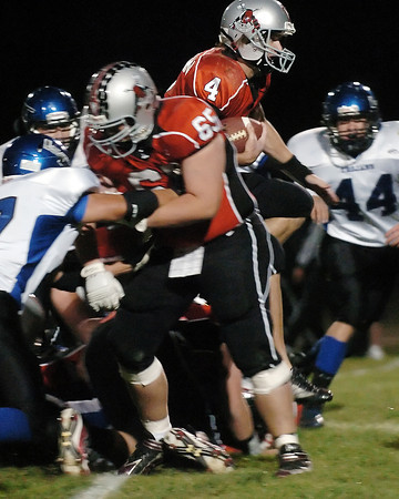 Loveland High School quarterback Scott Weissmann (4) busts through a hole in the line behind the block of teammate Eric Woodward (65) in the first quarter of their game against Longmont on Thursday, Oct. 28, 2010 at Patterson Stadium.