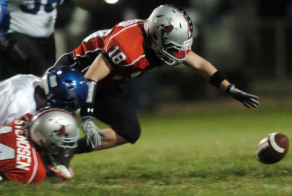 Loveland High School senior Ben Johnson (18) recovers a Longmont fumble in front of teammate Taylor Svendsen and Longmont's Mikal Merrill in the first quarter of their game on Thursday, Oct. 28, 2010 at Patterson Stadium.