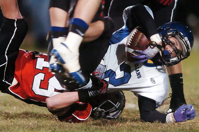 Longmont High School senior Cameron Herbert (2) is tackled by Loveland defender Geoff Call after a reception in the second quarter of their game on Thursday, Oct. 28, 2010 at Patterson Stadium.