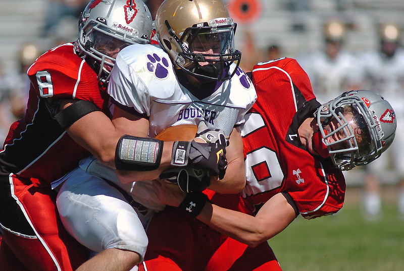 Loveland High School defenders Matt Walkowicz (8) and Geoff Call (19) combine to tackle Boulder running back Abel Brown in the second quarter of their game Saturday afternoon at Patterson Field. The Indians won, 13-7.