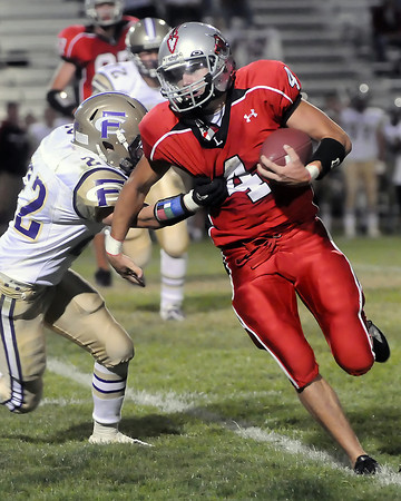 Loveland High School quarterback Scott Weissmann runs around Fort Collins defender Brady Mosbrucker in the second quarter of their game on Thursday, Sept. 2, 2010 at Patterson Stadium.
