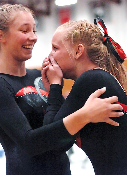 Loveland High School's Dayna Wadman, right, is congratulated by teammate Jana Schmitt after Wadman completed her second vault during a regional gymnastics meet on Friday at LHS.