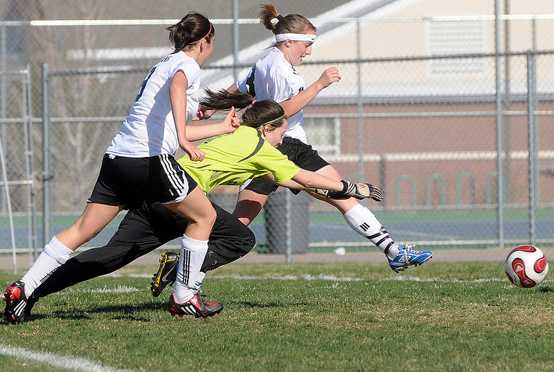 Loveland High School sophomore Kiara Gogarty, back, scores a first-half goal past Thornton goalie Caitlyn Hutchinson as Loveland's Ashley Gleason looks on during their game Wednesday, April 14, 2010 at the Mountain View soccer field. The Indians won, 10-0.
