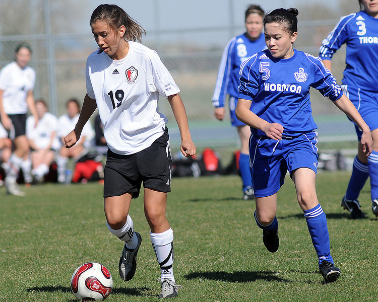Loveland High School senior Ashley Gleason dribbles the ball ahead of Thornton's Maria Cortez in the first half of their game on Wednesday, April 14, 2010 at the Mountain View soccer field. The Indians won, 10-0.