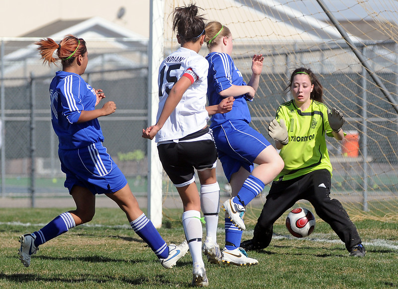 Loveland High School junior Molli Keeler (15) gets the ball past Thornton goalie Caitlyn Hutchinson for a score in the first half of their game Wednesday at the Mountain View soccer field. Keeler had three goals for the Indians' in their 10-0 victory over the Trojans.