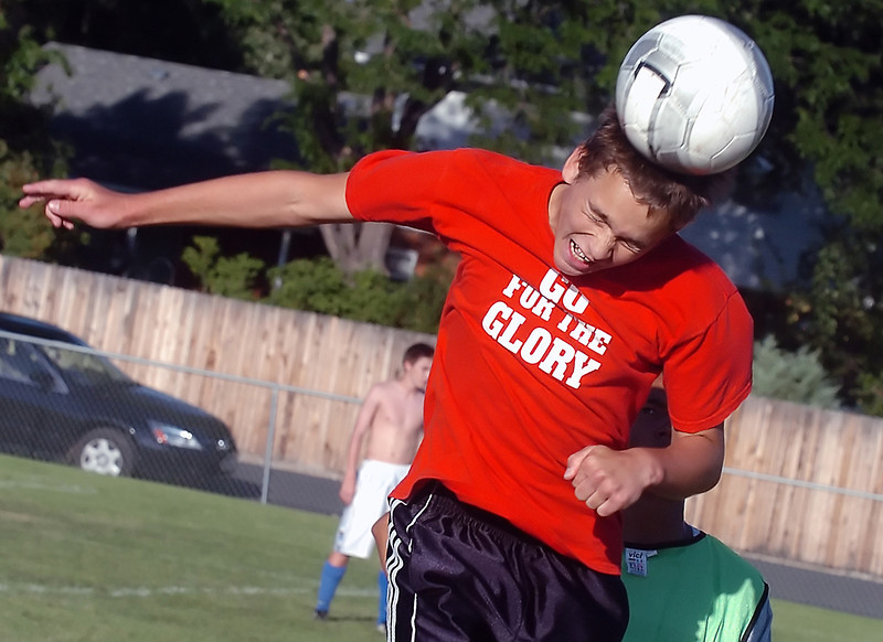 Loveland High School freshman Nick Grindy heads the ball while participating in a drill with senior Ryan Mayhew, right, during soccer practice Wednesday evening outside the school.