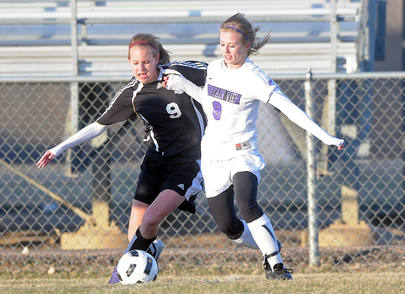 Loveland High School senior Chelsea Glanzer, left, and Mountain View junior Sarah Ross battle for control of the ball in the first half of their game Tuesday, March 22, 2011 at Patterson Stadium.