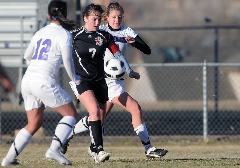 Loveland High School senior Taylor Schneider (7) tracks down the ball between Mountain View's Chelsey Brady, left, and Rikelle Berry in the first half of their game Tuesday at Patterson Stadium. Schneider later scored the game-winning goal in the second half of the Indians' 3-2 victory.