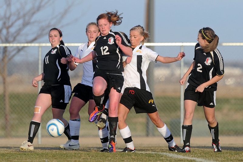 Loveland High School's Payton Rausch (12) and Thompson Valley's Tori Briggs collide while going after the ball in the second half of their game Tuesday, March 20, 2012 at the Mountain View soccer field.