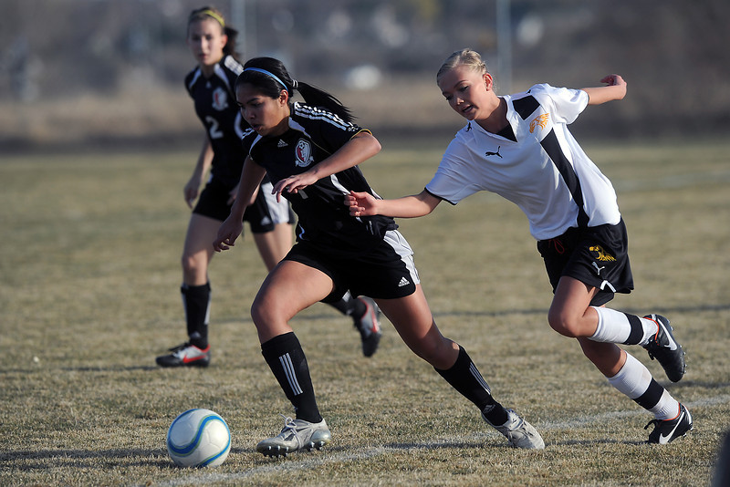Thompson Valley High School senior Tori Briggs, right, pursues Loveland's Greta Grainda in the first half of their game Tuesday, March 20, 2012 at the Mountain View soccer field.