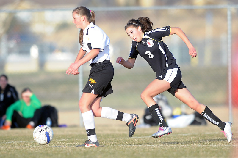 Loveland High School defender Allison Gleason, right, pursues Thompson Valley's Kaylyn Maston in the second half of their game Tuesday, March 20, 2012 at the Mountain View soccer field.