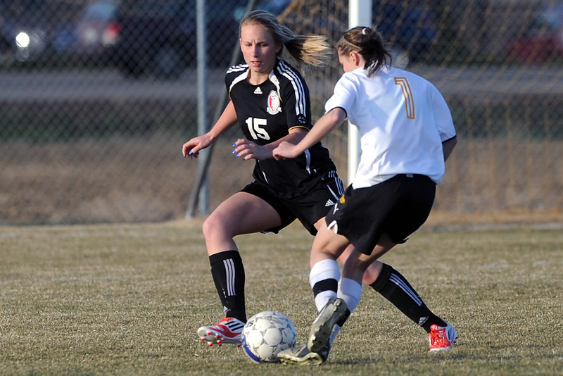 Loveland High School defender Katie Peterson, left, converges on Thompson Valley's Allie Davis in the second half of their game Tuesday, March 20, 2012 at the Mountain View soccer field.