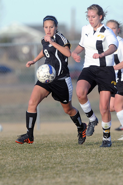 Loveland High School junior Kat Bossenbrek, left, and Thompson Valley junior Paige Chase track down the ball in the second half of their game Tuesday, March 20, 2012 at the Mountain View soccer field.