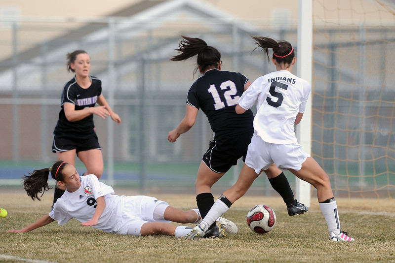 Loveland High School's Nicole Stackhouse, bottom, slides for the ball as she and teammate Kendra Neubert, right, try to score past Mountain View defenders Alexis Ruhman, back left, and Payton Rausch (12) in the first half of their game Tuesday, March 13, 2012 at MVHS.